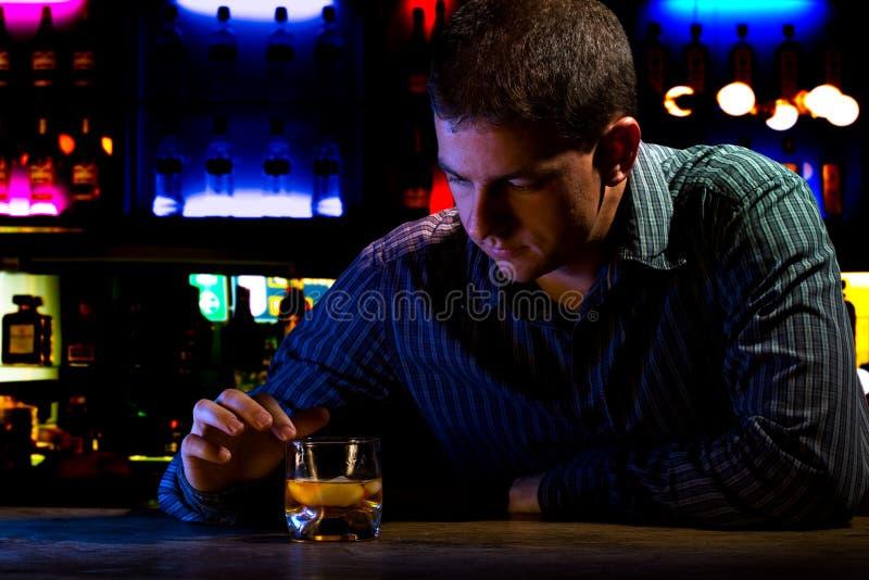 Homem preocupado que senta-se na barra fotografia de stock royalty free