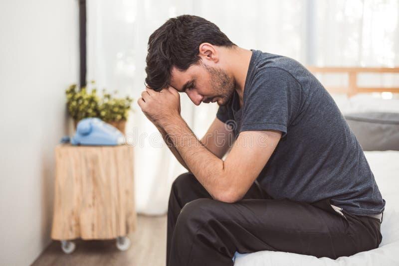 Homem preocupado que senta-se na cama com m?o na testa no quarto na emo??o s?ria do humor Major Depressive Disorder chamou o conc imagem de stock