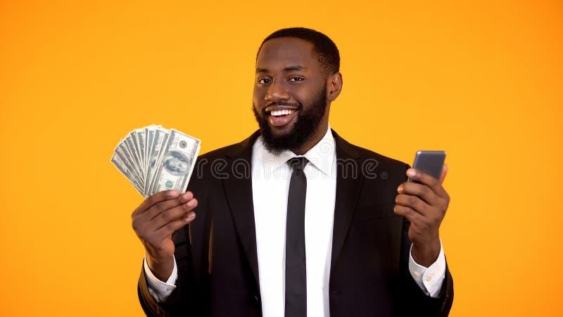 Homem preto bem sucedido de sorriso no telefone da terra arrendada do terno e nas notas de d?lar, cashback foto de stock royalty free