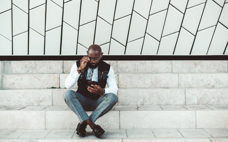 Homem preto da forma com um smartphone imagem de stock