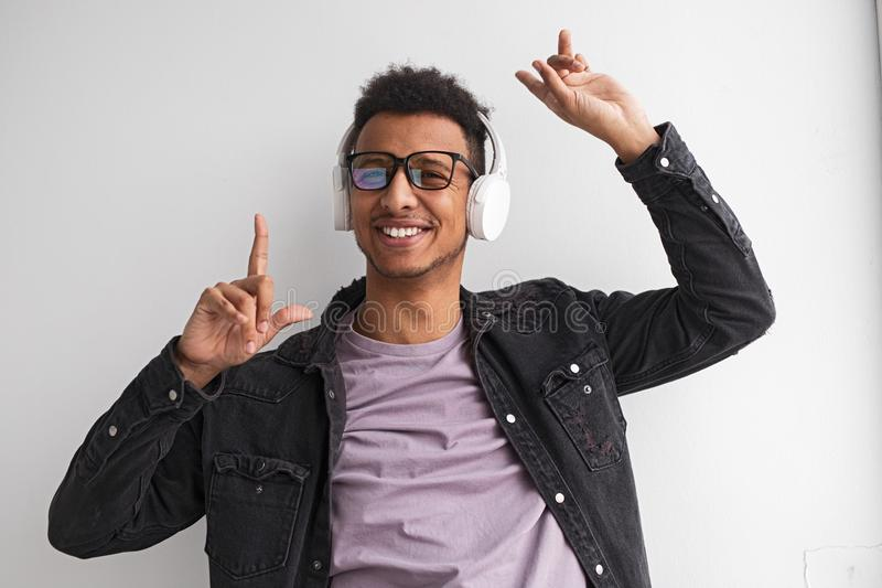 Homem preto de sorriso que escuta a música e a dança imagens de stock royalty free
