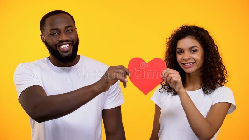 Homem preto e câmera de sorriso guardando fêmea do coração de papel, conexão das relações imagens de stock