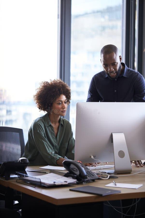 Homem preto novo e colegas fêmeas que trabalham junto em um computador em um escritório criativo, vertical imagens de stock royalty free