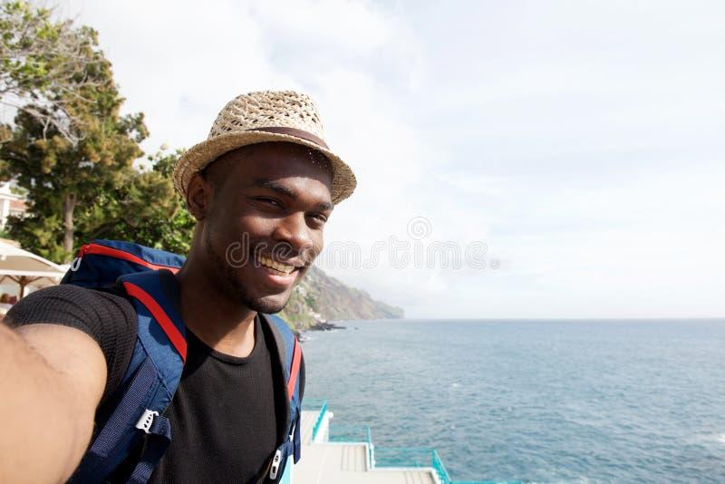 Homem preto novo feliz do curso que sorri ao tomar o selfie pelo mar imagens de stock