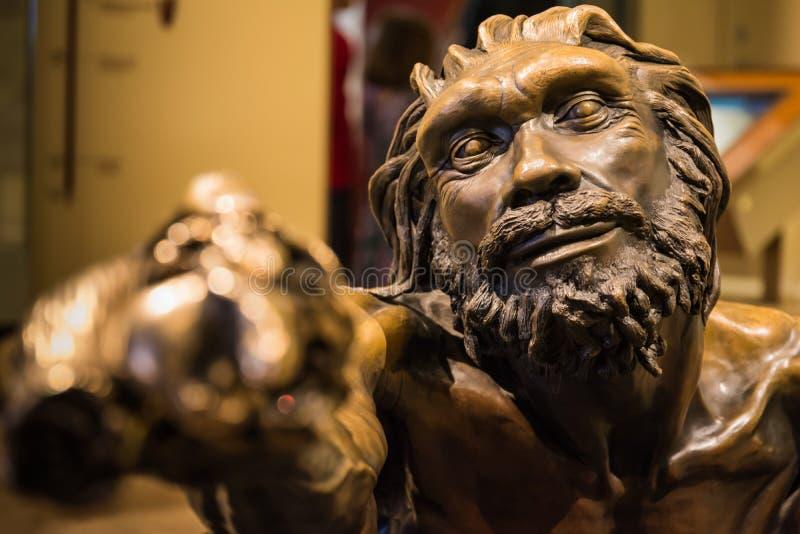 Homem primitivo que guarda a característica H da instalação do bronze da estátua da vara fotos de stock royalty free