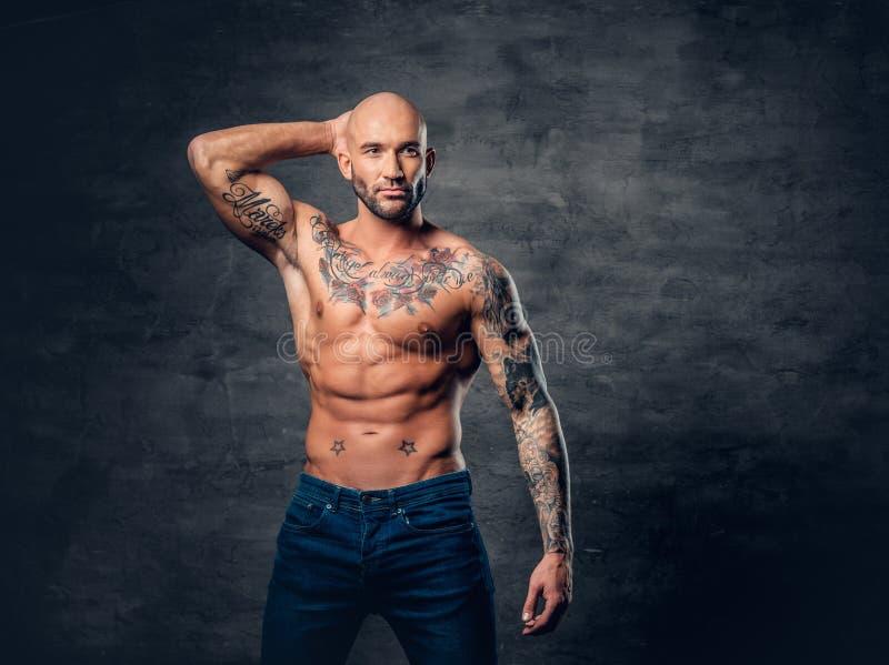 Homem principal, muscular barbeado com tatuagens em seu torso sobre v cinzento fotos de stock royalty free
