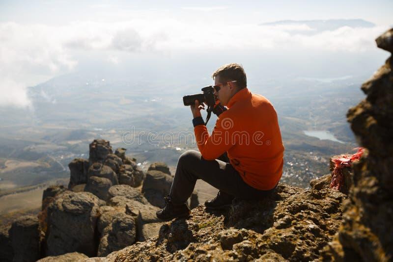 Homem profissional novo do viajante com a câmera do dslr que dispara na paisagem fantástica exterior da montanha O caminhante sen fotografia de stock