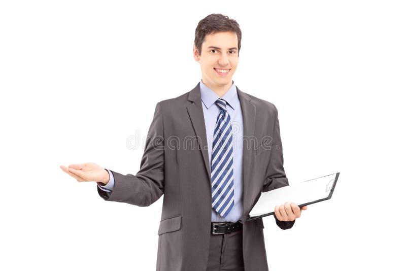 Homem profissional novo que guardara uma prancheta e que gesticula com ha imagem de stock royalty free