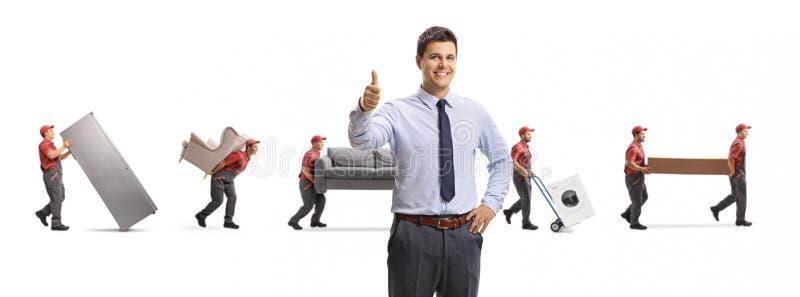 Homem profissional novo que mostra os polegares acima e os motores que levam a mobília foto de stock
