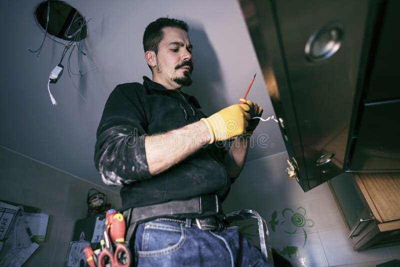 Homem profissional que repara luzes da cozinha imagem de stock royalty free
