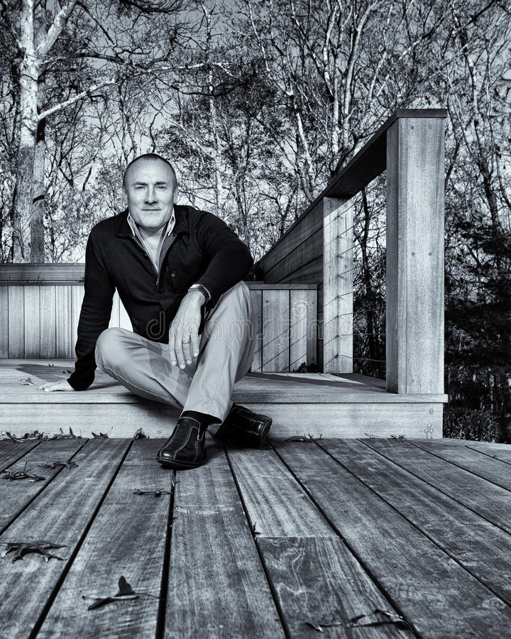 Homem profissional sentado no decking do jardim imagem de stock