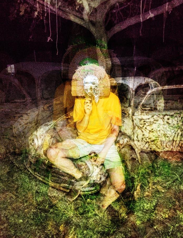 Homem psicadélico da máscara do crânio do horror do pulso aleatório no fundo abandonado do carro fotografia de stock royalty free