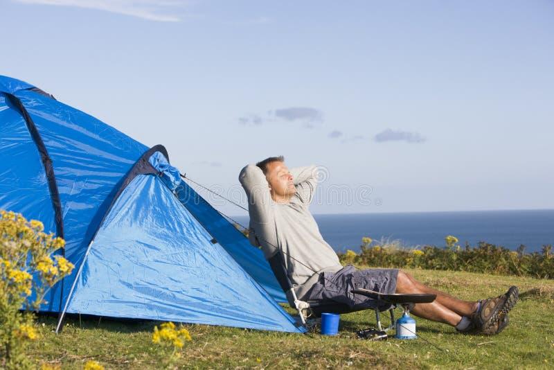 Homem que acampa ao ar livre e que cozinha