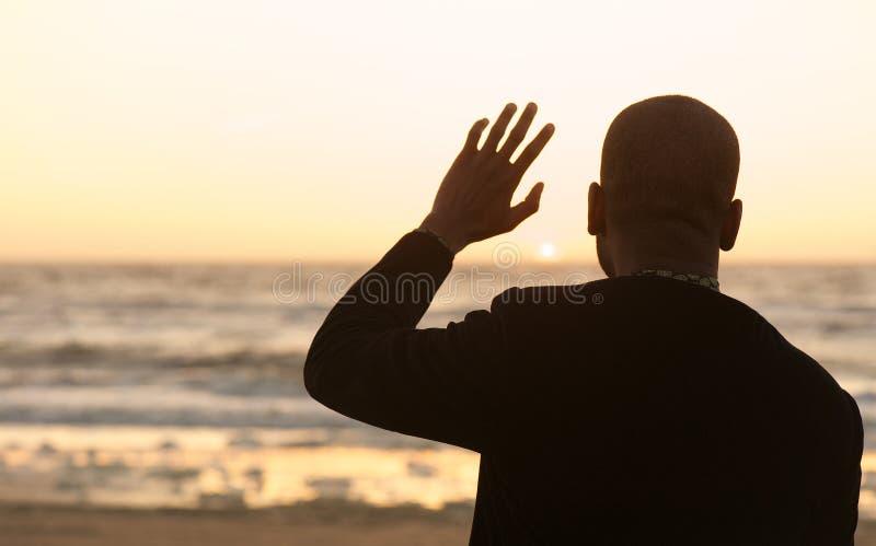 Homem que acena no por do sol