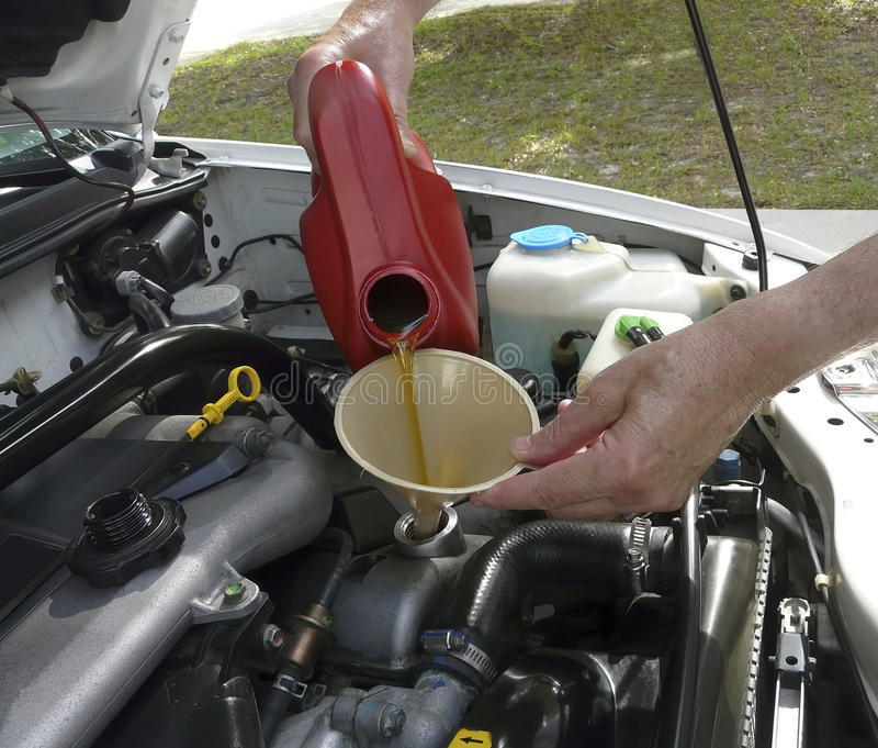 Homem que adiciona o óleo de motor ao carro fotografia de stock