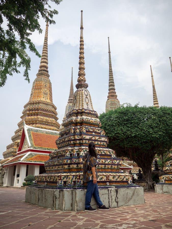 Homem que admira chedis em Wat Pho, Banguecoque, Tailândia foto de stock