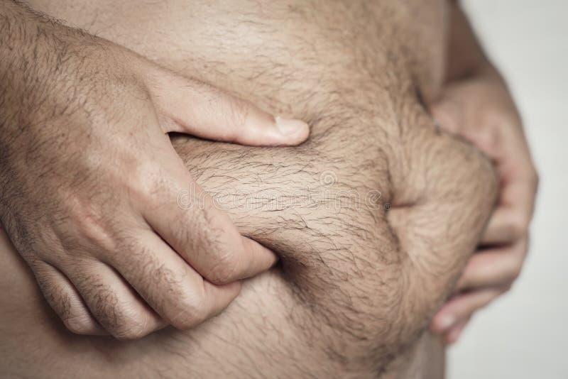 Homem que agarra a gordura de seu estômago foto de stock royalty free