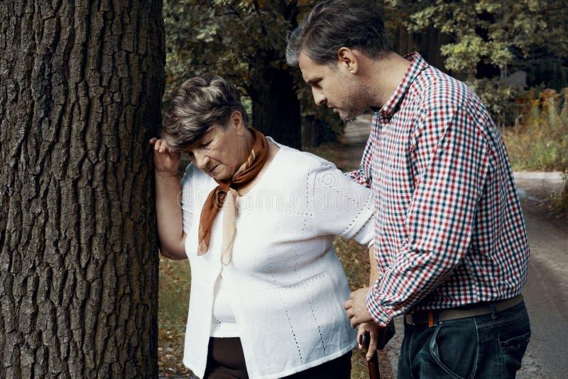 Homem que ajuda a mulher idosa fraca com ataque da dispneia durante a caminhada fotografia de stock royalty free