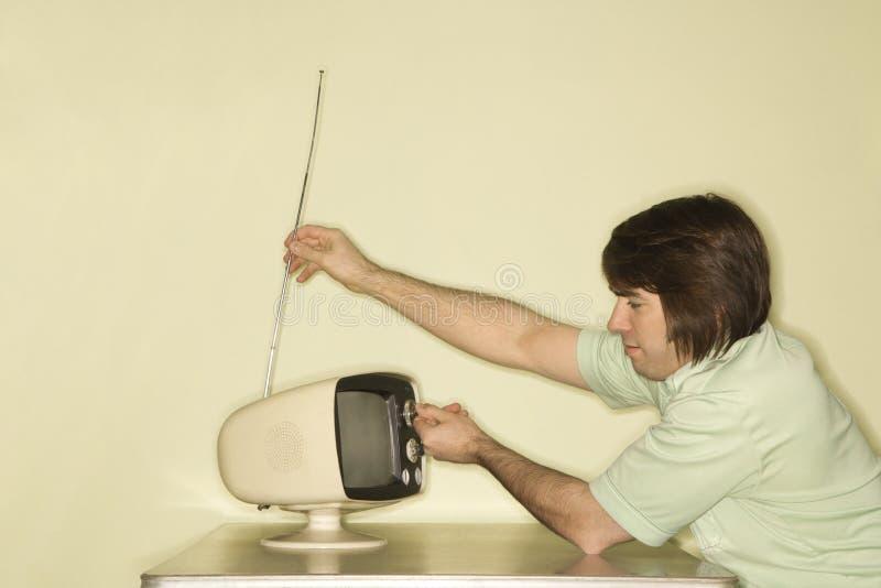 Homem que ajusta na televisão. imagens de stock