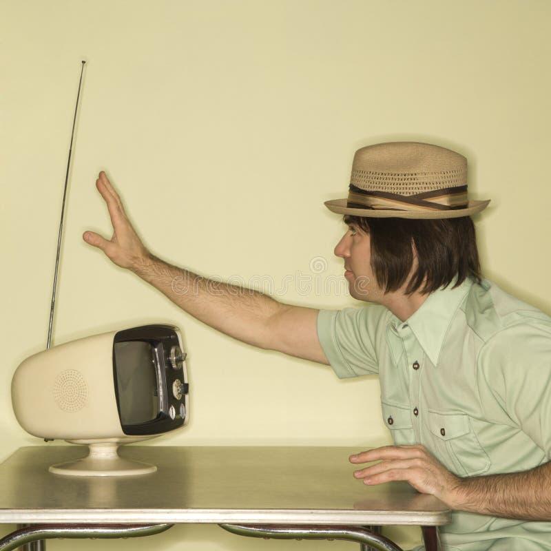Homem que ajusta na televisão. fotos de stock royalty free