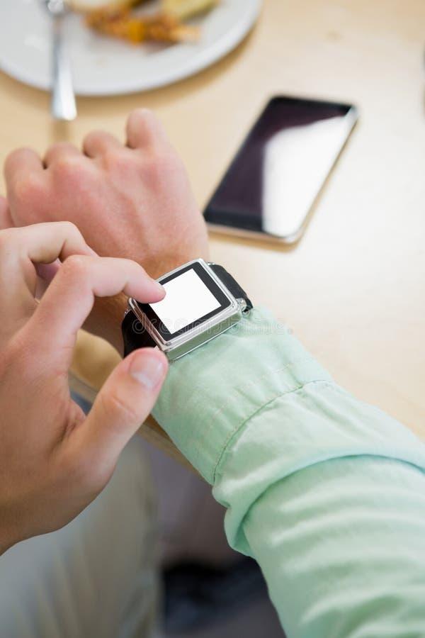 Homem que ajusta o tempo em seu smartwatch fotos de stock