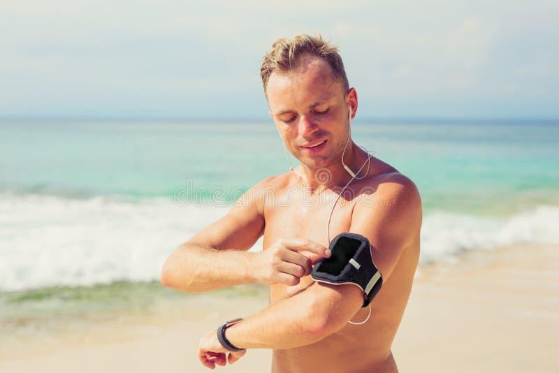 Homem que ajusta seu telefone celular antes da sessão do exercício imagens de stock royalty free