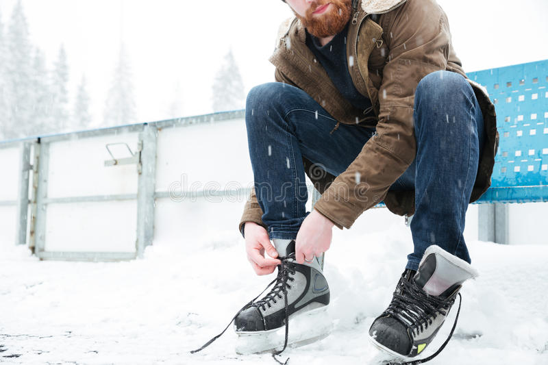 Homem que amarra o laço em patins de gelo fora imagens de stock royalty free