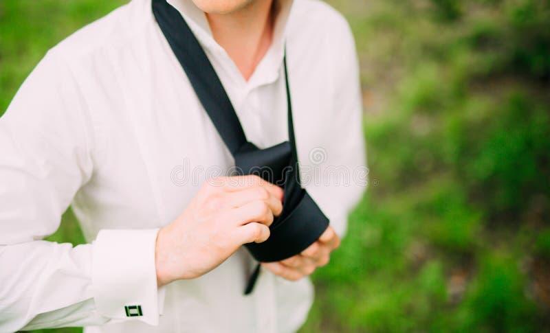 Homem que amarra seu laço O noivo que amarra o seu laço Acesso do noivo do casamento fotos de stock