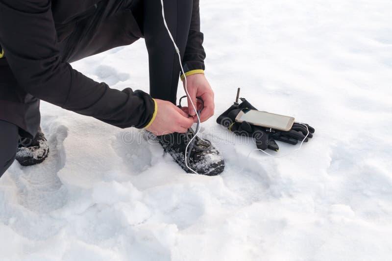 Homem que amarra tênis de corrida na neve fotografia de stock royalty free