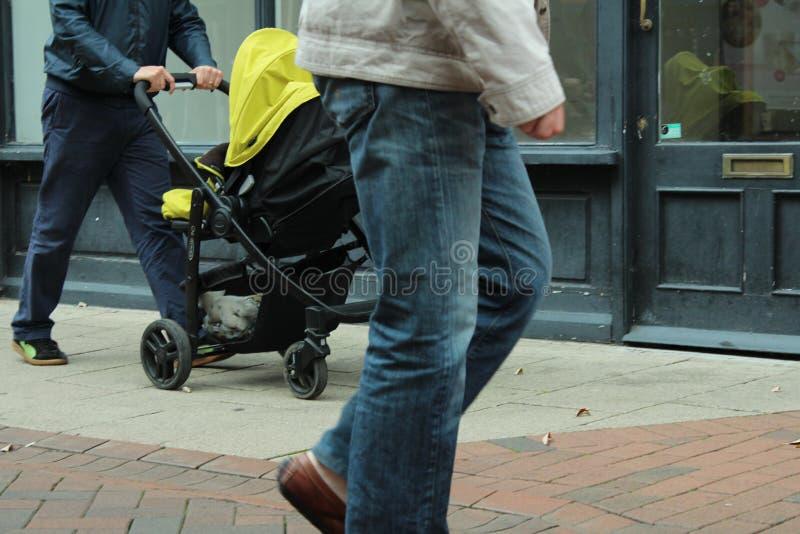 Homem que anda com caminhante do bebê imagem de stock