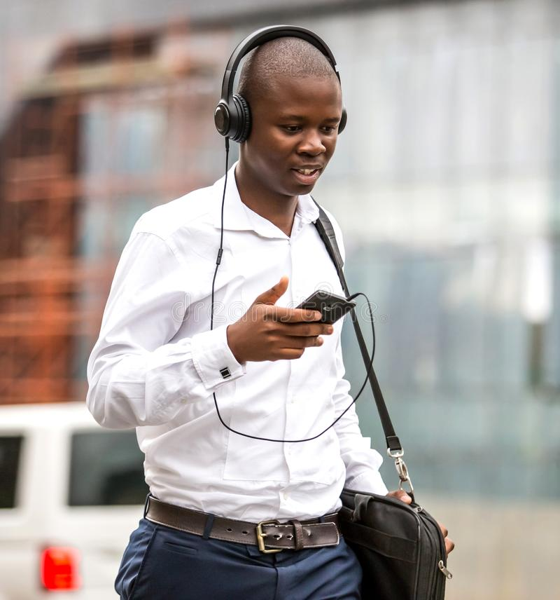 Homem que anda com os fones de ouvido na cidade foto de stock