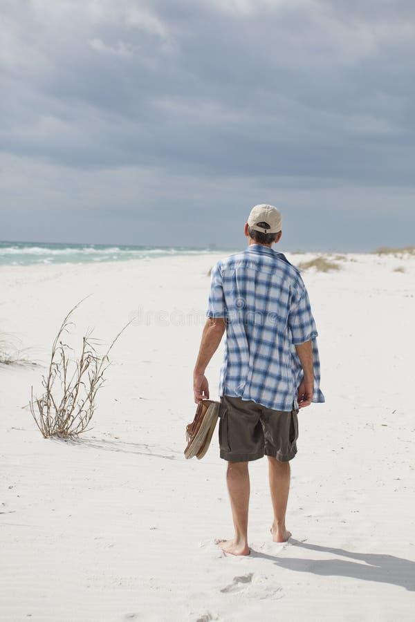 Homem que anda em uma praia bonita foto de stock