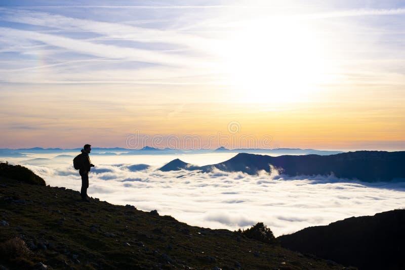 Homem que anda entre montanhas com um mar das nuvens fotos de stock