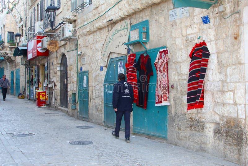 Homem que anda lojas velhas da rua da cidade, Bethlehem foto de stock
