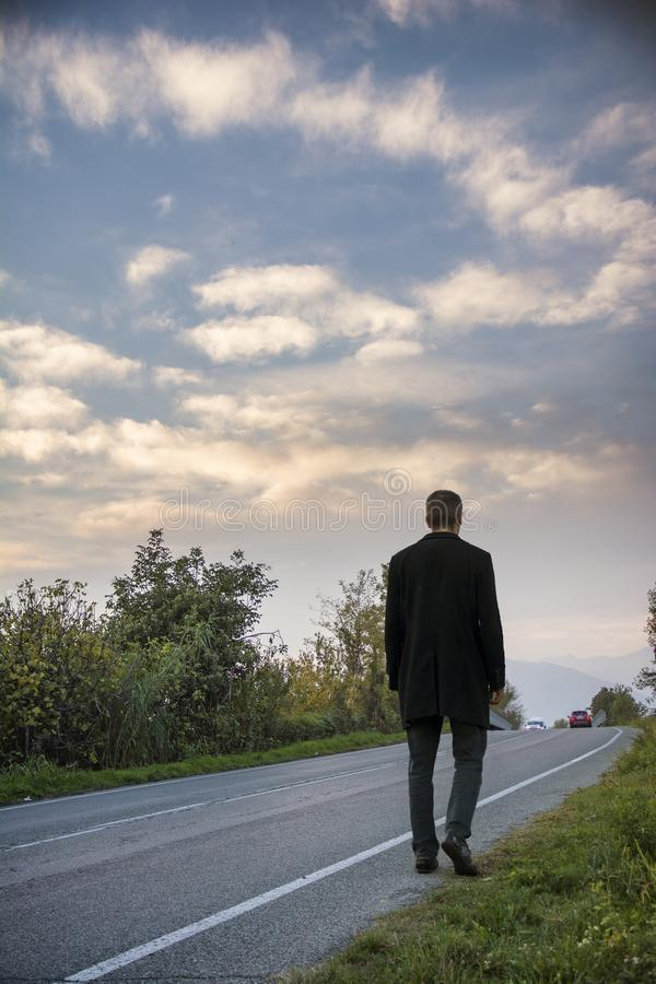 Homem que anda na borda da estrada foto de stock