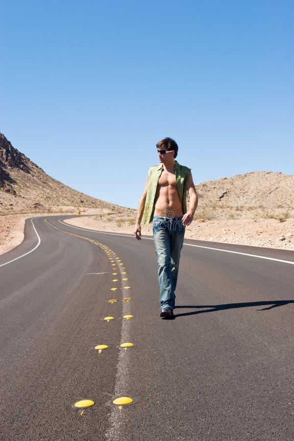 Homem que anda na estrada fotografia de stock royalty free