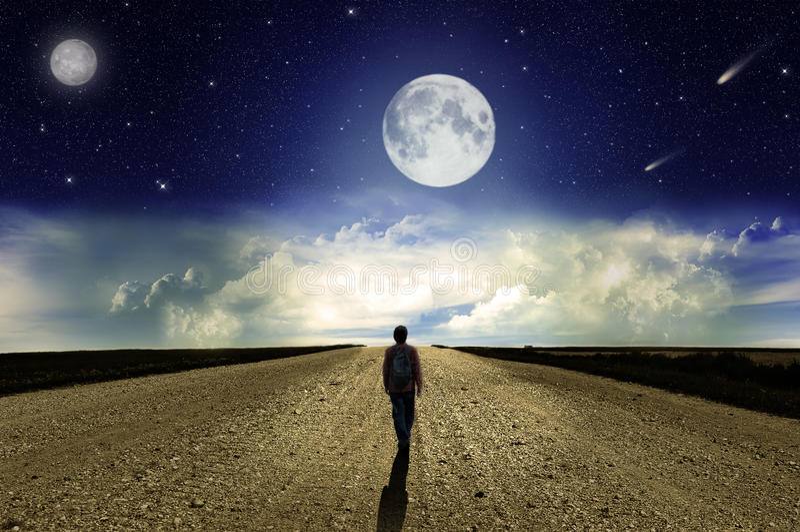 Homem que anda na estrada na noite fotografia de stock royalty free