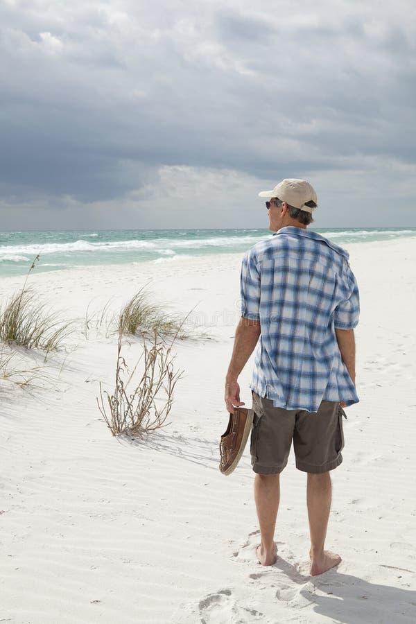 Homem que anda na praia como novo bonita foto de stock