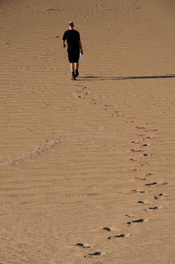 Homem que anda no deserto imagem de stock