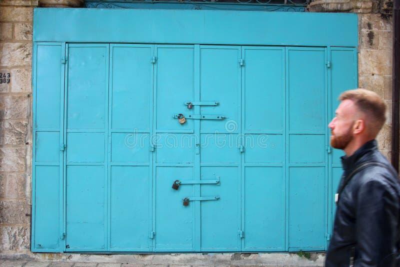 Homem que anda portas azuis da gasolina velha, Jerusalém, Israel fotos de stock royalty free