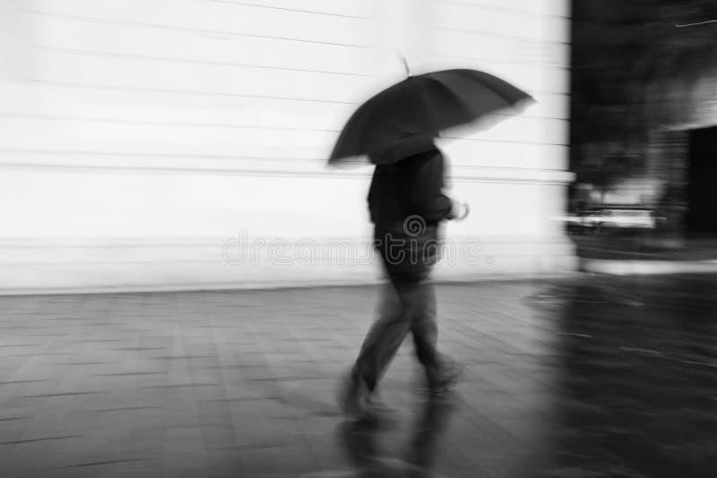 Homem que anda sob o guarda-chuva fotografia de stock