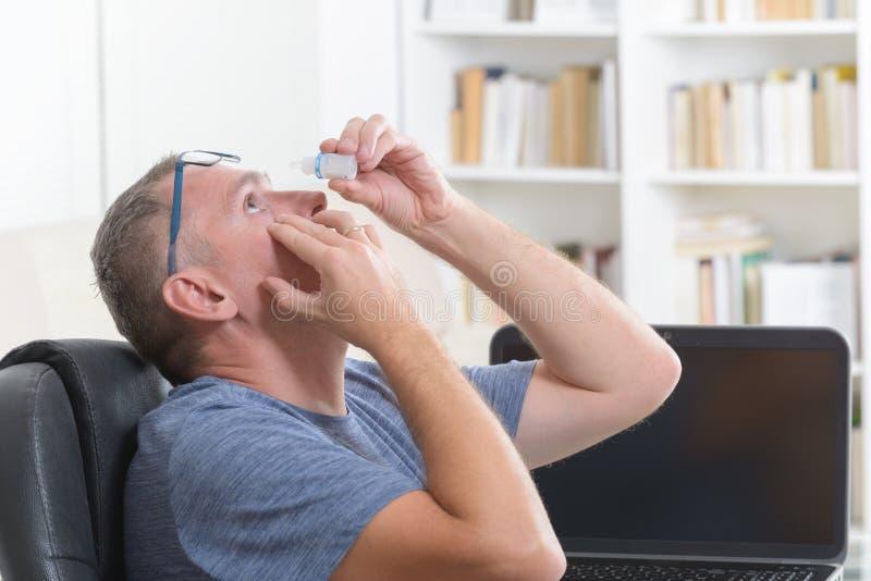 Homem que aplica gotas de olho imagem de stock