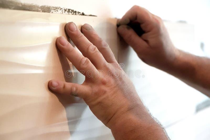 Homem que aplica o azulejo a uma parede da cozinha foto de stock