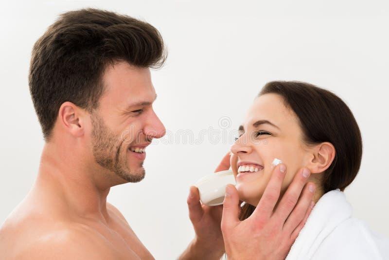 Homem que aplica o creme hidratante no mordente da mulher imagem de stock royalty free