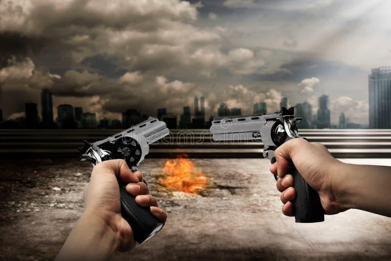Homem que aponta a arma dois queimar a cidade fotos de stock royalty free