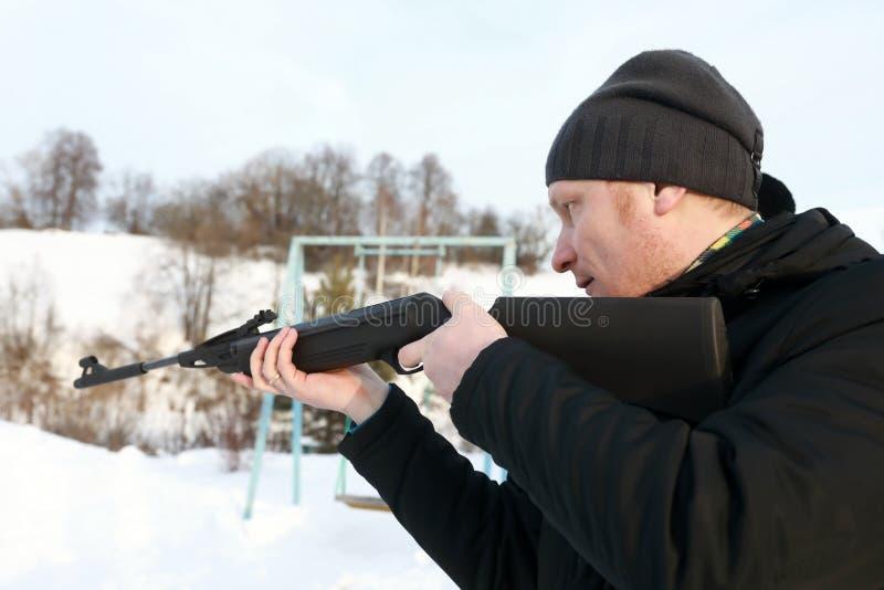 Homem que aponta com rifle de ar foto de stock royalty free