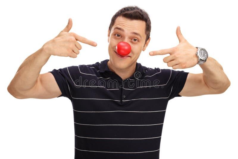 Homem que aponta em seu nariz vermelho do palhaço imagem de stock royalty free