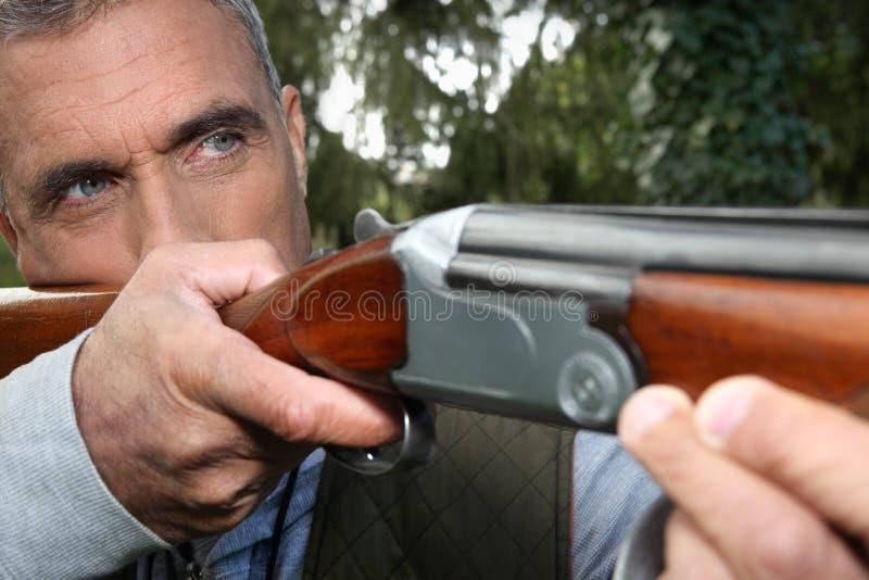 Homem que aponta um rifle fotografia de stock
