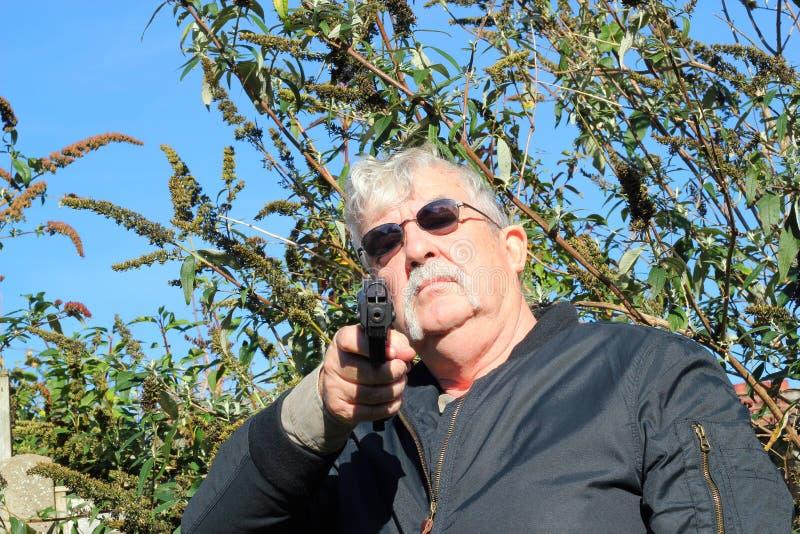 Homem que aponta uma arma para baixo. imagens de stock