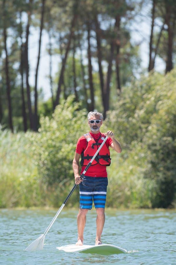 Homem que aprecia o passeio no lago com paddleboard foto de stock